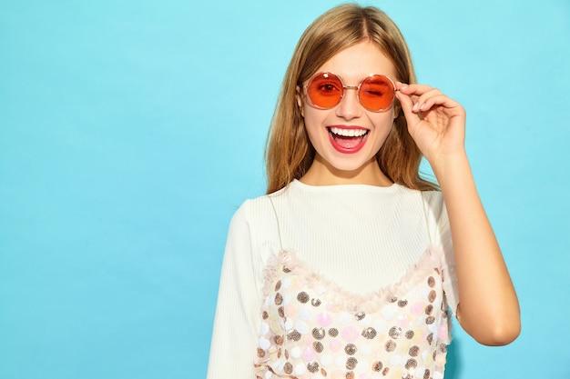 若い美しい女性。サングラスでウインクカジュアルな夏服のトレンディな女性。肯定的な女性の感情表情ボディランゲージ。青い壁に分離された面白いモデル