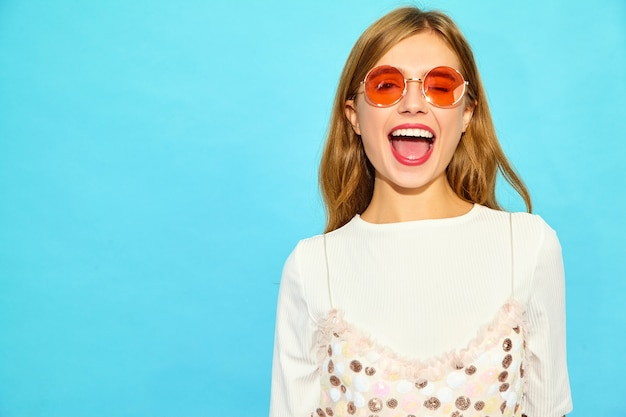 若い美しい女性。サングラスのカジュアルな夏服のトレンディな女性。肯定的な女性の感情表情ボディランゲージ。青い壁に分離された面白いモデル