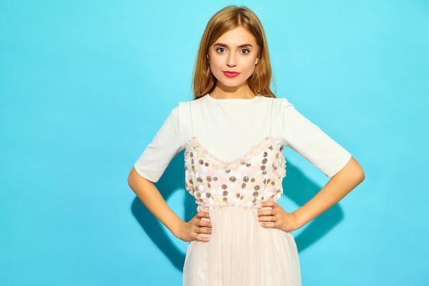 若い美しい女性。カジュアルな夏服のトレンディな女性。青い壁に分離された肯定的な女性モデル