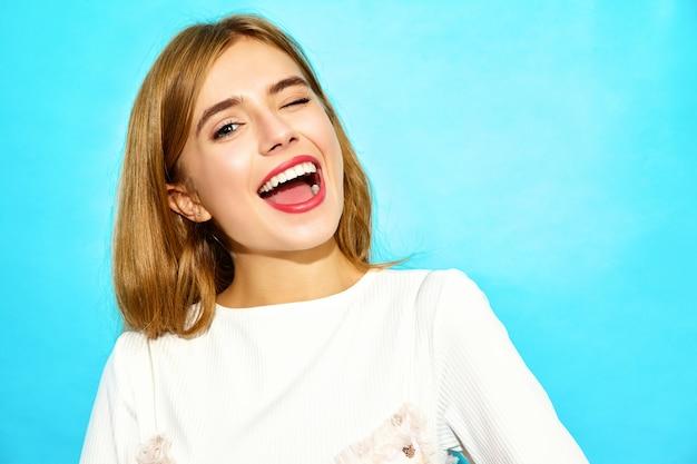 Молодая красивая женщина модная женщина в повседневной летней одежде подмигивая. смешная модель на синей стене
