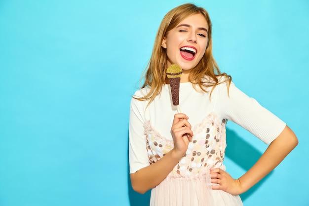 小道具偽のマイクで歌う若い美しい女性。カジュアルな夏服のトレンディな女性。青い壁に分離された面白いモデル
