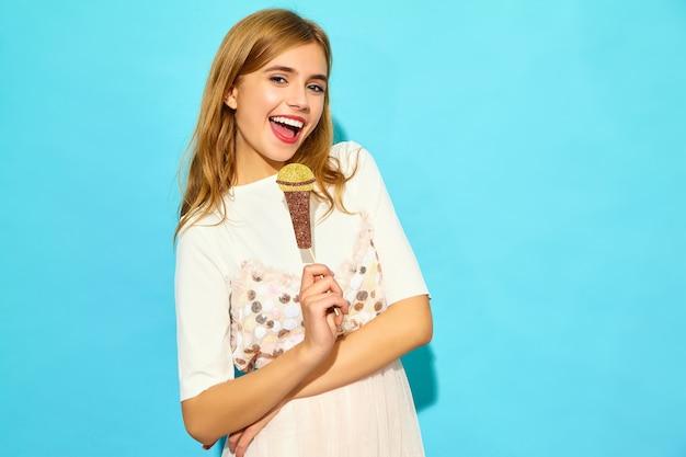小道具偽のマイクで歌う若い美しい女性。カジュアルな夏服のトレンディな女性。