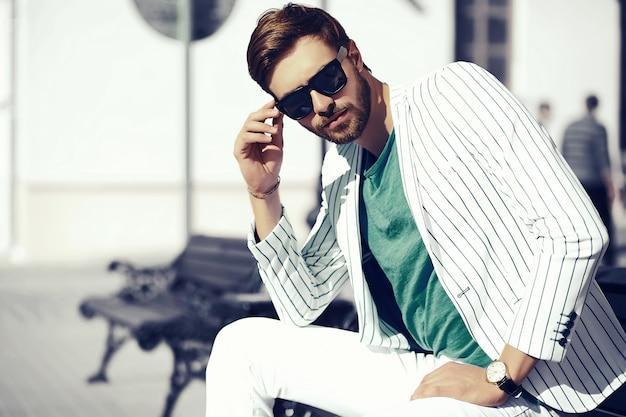 サングラスの通りのスーツ布ライフスタイルで若いスタイリッシュな自信を持って幸せなハンサムな実業家モデル