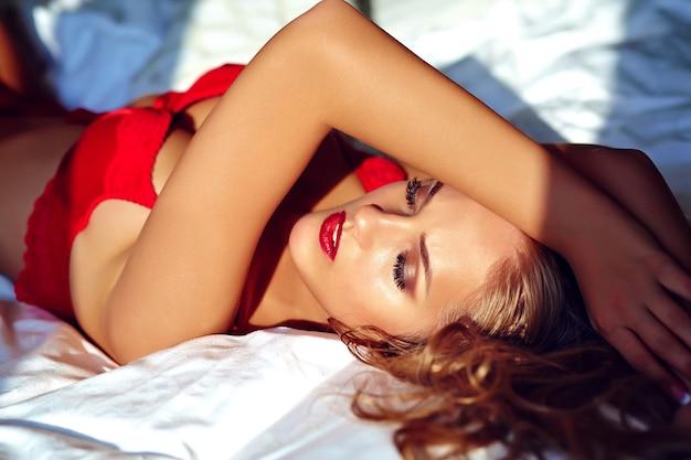 朝日の出で白いベッドに横たわっている赤のエロティックなランジェリーを着ている美しいセクシーな若い大人の金髪女性モデルのファッションポートレート