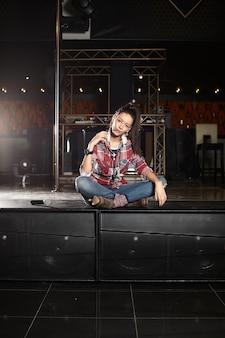 クラブのシーンに座っているマイクを使って若い美しい笑顔ポップスター歌手