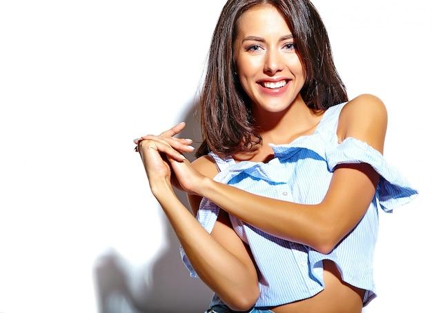 白い壁に化粧がないカジュアルな夏服で美しい女性モデルの肖像画
