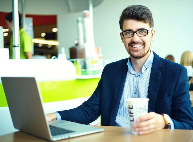 Молодой модный улыбающийся хипстерский человек, пьющий кофе в городском кафе во время обеда с ноутбуком в костюме