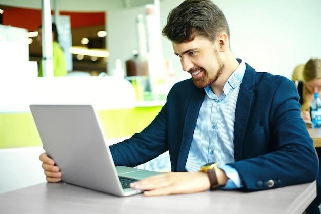 若者のファッションスーツのノートブックと昼食時に市のカフェで流行に敏感な男の笑みを浮かべて