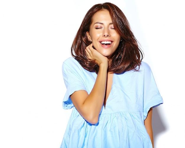 白い壁に化粧のないカジュアルな青いヒップスター夏服に夢中になる陽気な笑顔ファッション女性の肖像画