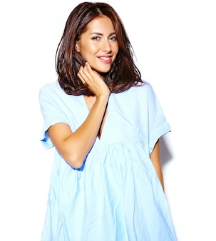Портрет веселой улыбающейся женщины моды, сходящей с ума в повседневной синей хипстерской летней одежде без макияжа на белой стене