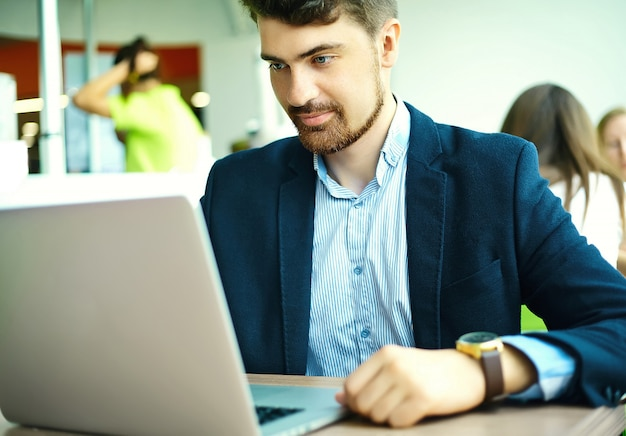 Молодой модный улыбающийся битник человек в городском кафе во время обеда с ноутбуком в костюме