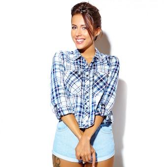 白い壁に化粧なしでカジュアルな夏の市松模様のシャツで美しい女性モデルの肖像画