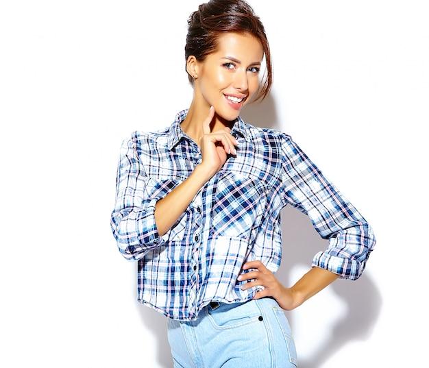 白い壁に化粧なしでカジュアルな流行に敏感な市松模様のシャツに夢中になる陽気な笑顔ファッション女性の肖像画
