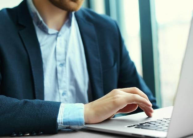 若い男がノートパソコン、ノートパソコン、職場での事業者の男の手での作業