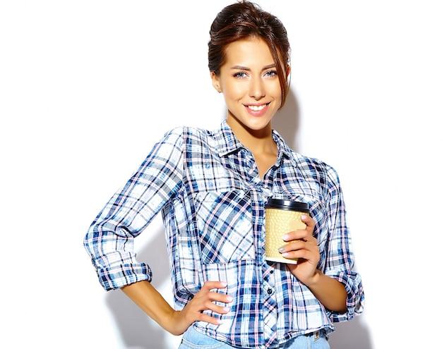 Портрет красивой стильной прохладной подростковой женщины в клетчатой рубашке, держа пластиковую чашку кофе