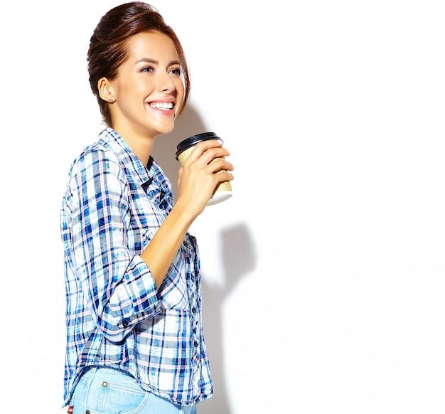 Портрет красивой стильной прохладной подростковой женщины в клетчатой рубашке, держа пластиковый кофе кубок.
