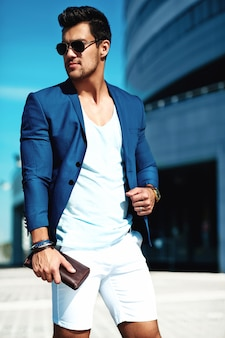 通りでポーズをとってエレガントなスーツに身を包んだセクシーなハンサムなファッションの男性モデル男の肖像。青空