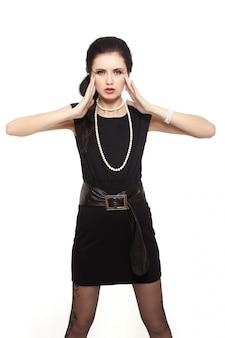 Красивая сексуальная женщина с красными губами в маленьком черном платье на белом