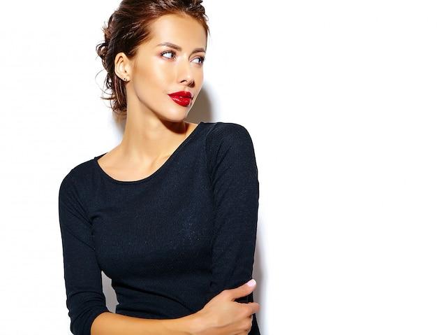 Красивая счастливая милая сексуальная брюнетка женщина в черном платье с красными губами на белой стене