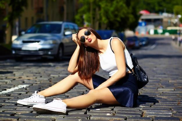 Девушка посылает воздушный поцелуй сидя на улице