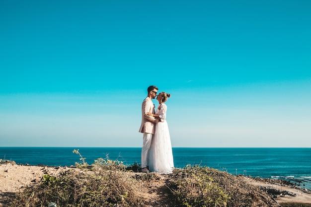 Жених и невеста позируют на скале за голубым небом и морем