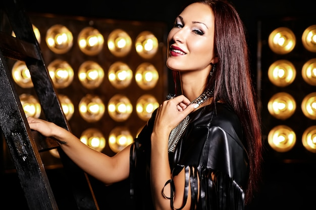 Красивая девушка в черной одежде позирует со студийными огнями