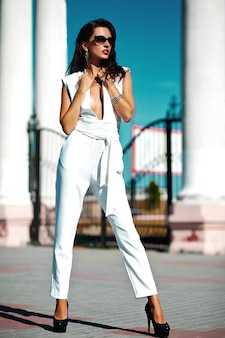 Красивая брюнетка на улице в белом джемпере
