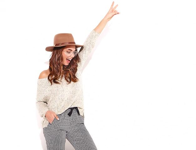 Портрет молодой стильной девушки модели в случайные летние одежды в коричневой шляпе с естественным макияжем в очках изолированы. и показывая знак мира