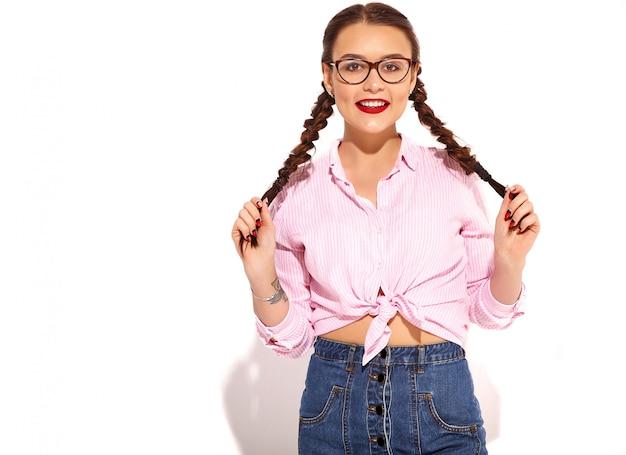 Портрет молодой счастливой улыбающейся модели женщины с ярким макияжем и красными губами с двумя косичками в летней разноцветной розовой рубашке