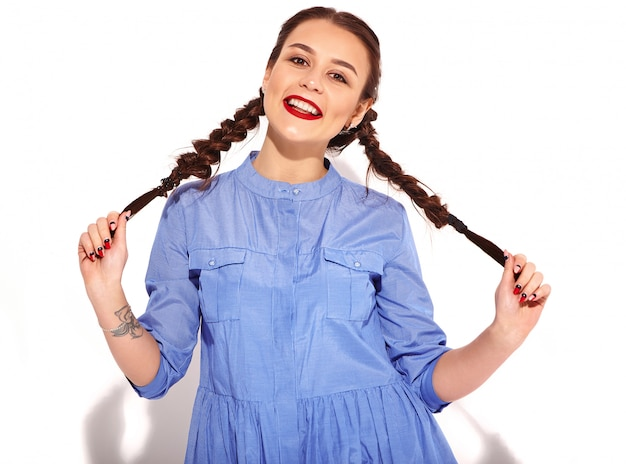 Портрет молодой счастливой улыбающейся женщины модели с ярким макияжем и красными губами с двумя косичками в руках в летнее разноцветное синее изолированное платье