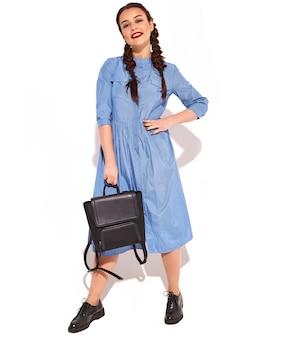 Портрет молодой счастливой улыбающейся модели женщины с ярким макияжем и красными губами с двумя косичками в руках в летнем красочном синем изолированном платье и рюкзаке.