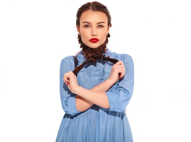 Портрет молодой счастливой улыбающейся модели женщины с ярким макияжем и красными губами с двумя косичками в руках в летнем разноцветном синем платье