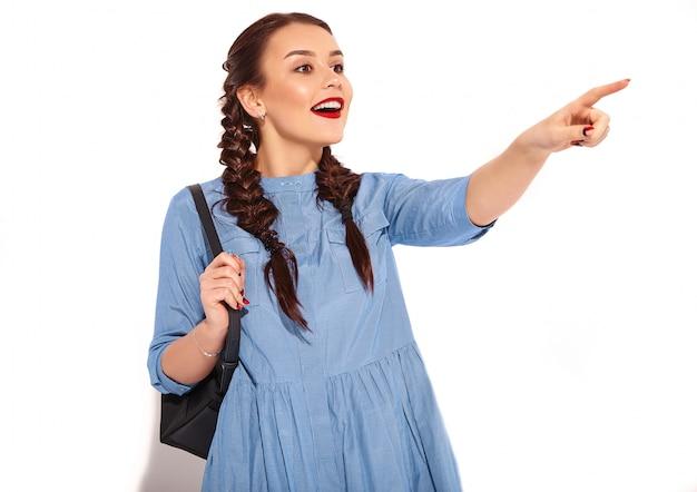 Портрет молодой счастливой улыбающейся модели женщины с ярким макияжем и красными губами с двумя косичками в руках в летнем красочном синем изолированном платье и рюкзаке. указывая в сторону