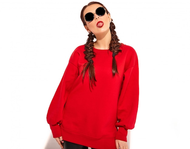 Молодая счастливая улыбающаяся модель женщины с яркой косметикой и красочными губами с двумя косичками и солнцезащитными очками в летней красной изолированной одежде. показывая ее язык