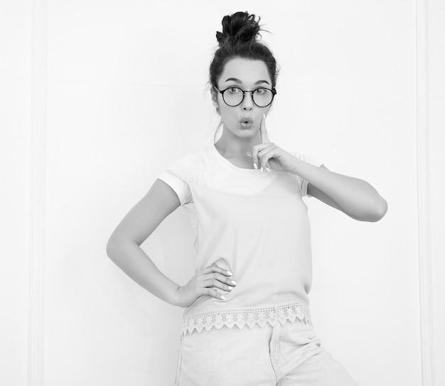 Портрет молодой красивой женщины брюнетка девушка модель с обнаженной макияж в красочных летних розовый битник одежду позирует возле стены. есть и идея