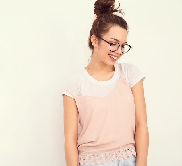 Портрет молодой красивой женщины брюнетка девушка модель с обнаженной макияж в красочных летних розовый битник одежду позирует возле стены.