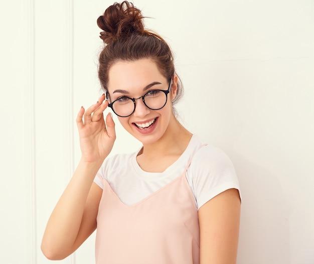壁に近いポーズカラフルな夏ピンクヒップスター服で裸化粧と若い美しいブルネットの女性少女モデルの肖像画。幸せそうに見える