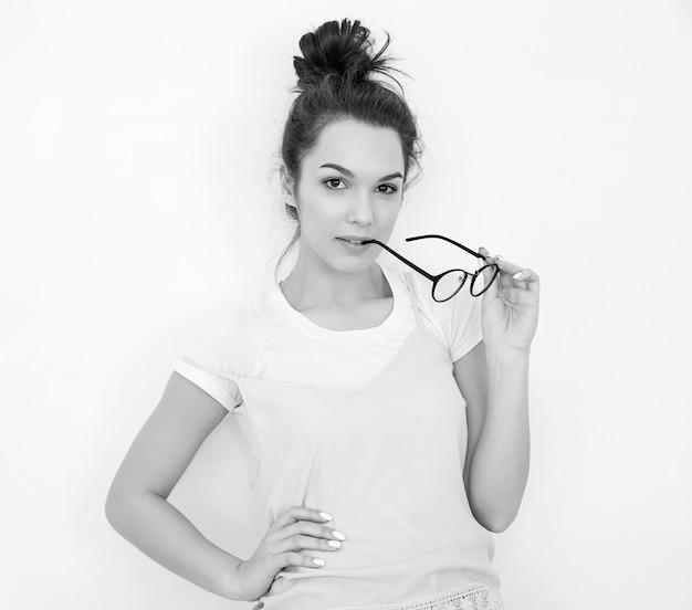 Портрет молодой красивой женщины брюнетка девушка модель с обнаженной макияж в красочных летних розовый битник одежду позирует возле стены. кусать очки