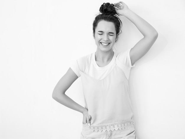 Портрет молодой красивой женщины брюнетка девушка модель с обнаженной макияж в красочных летних розовый битник одежду позирует возле стены. закрытые глаза