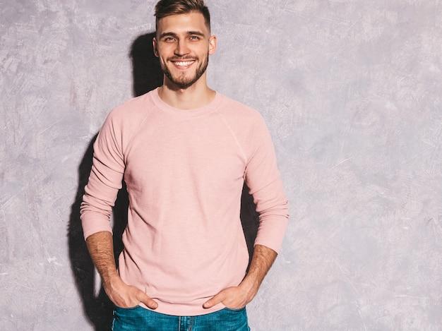 カジュアルな夏のピンクの服を着てハンサムな笑みを浮かべて流行に敏感なビジネスマンモデルの肖像画。