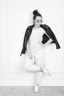 壁に近いポーズのサングラスで夏流行に敏感なバイカーレザージャケット服を着て裸化粧と若いブルネット美人少女モデルの肖像画。