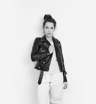 Портрет молодой красивой женщины брюнетка девушка модель с обнаженной макияж носить летние битник байкер кожаная куртка позирует возле стены.