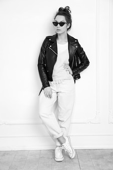 Портрет молодой красивой женщины брюнетка девушка модель с обнаженной макияж носить летние битник байкер кожаную куртку одежды в солнцезащитные очки, позирует возле стены.