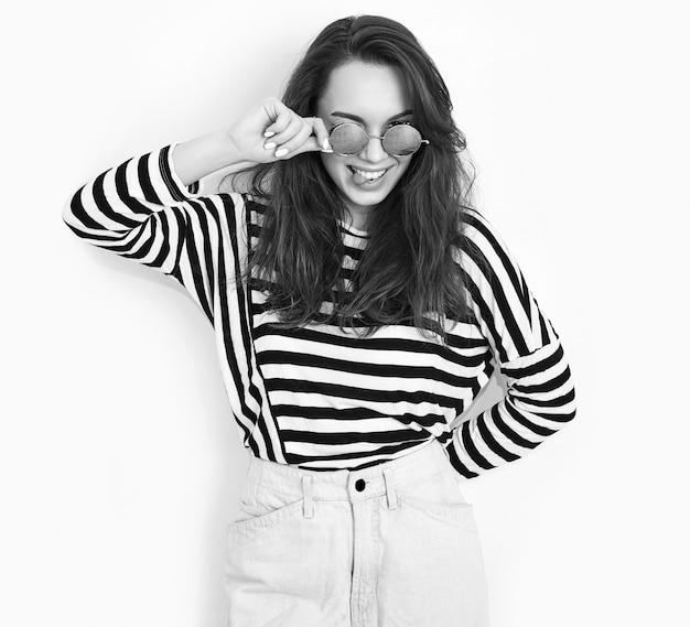 Портрет молодой красивой женщины брюнетка девушка модель с обнаженной макияж в летних битник одежду и солнцезащитные очки, позирует возле стены. показывая ее язык