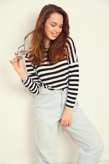 Портрет молодой красивой женщины брюнетка девушка модель с обнаженной макияж в летней одежде битник, позирует возле стены.