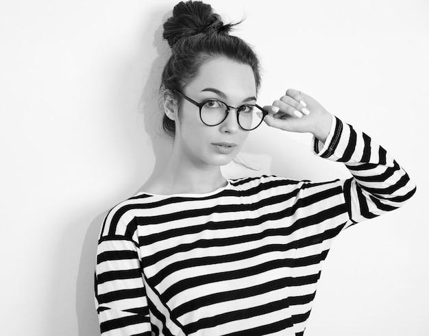 壁に近いポーズ夏流行に敏感な服のメガネで裸化粧と若い美しいブルネットの女性少女モデルの肖像画。