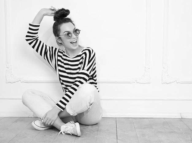 サングラスの壁に近いポーズをとって夏流行に敏感な服で裸化粧と若い美しいブルネットの女性少女モデルの肖像画。床に座って