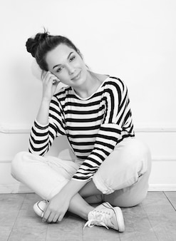 壁に近いポーズ夏流行に敏感な服で裸化粧と若い美しいブルネットの女性少女モデルの肖像画。床に座って