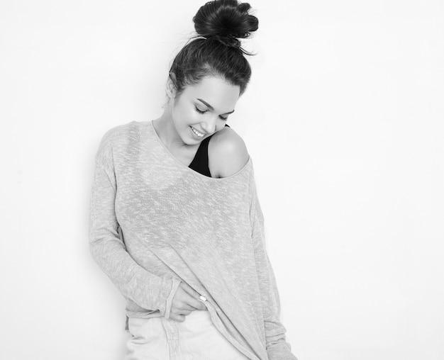 Портрет молодой красивой женщины брюнетка девушка модель с обнаженной макияж в летней одежде позирует возле стены.
