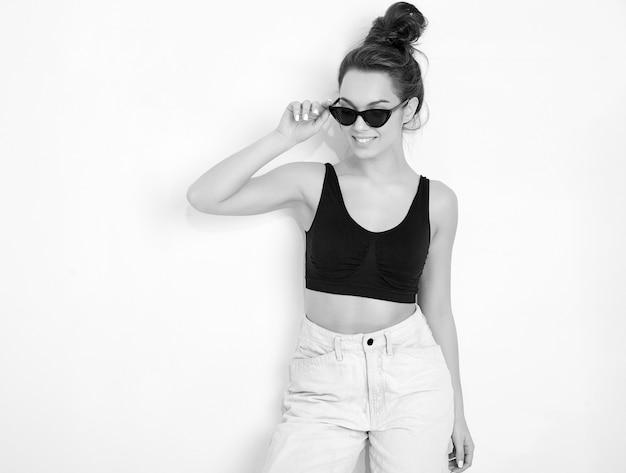 Портрет молодой красивой женщины брюнетка девушка модель с обнаженной макияж в летней футболке сверху и джинсовой одежде позирует возле стены.